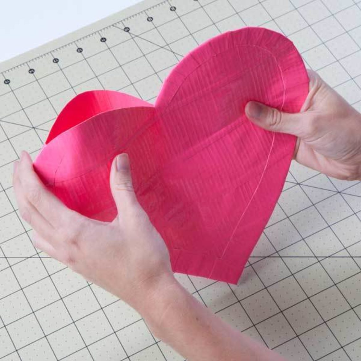 the two heart shapes from the previous steps taped together almost all the way around