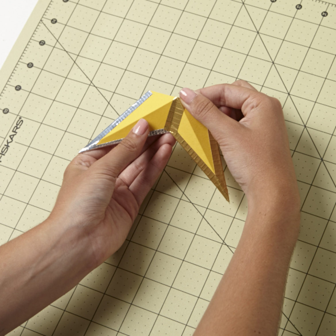 After creating another piece identical to the one taped together in the previous step, tape them together at the top of the diamond shape so that you have two of the the star's points