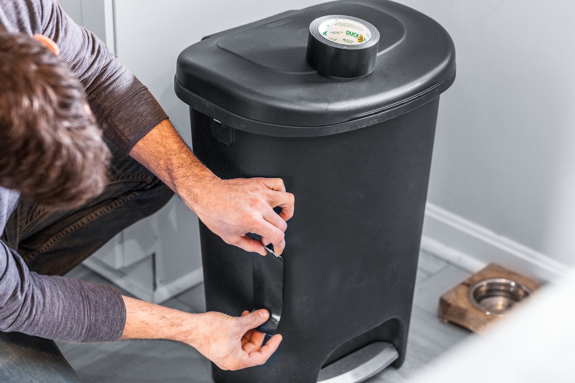 Man fixing crack in garbage can with black duct tape