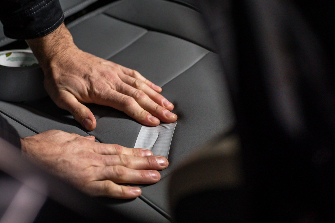 Man fixing rip in a car seat cushion with gray duct tape