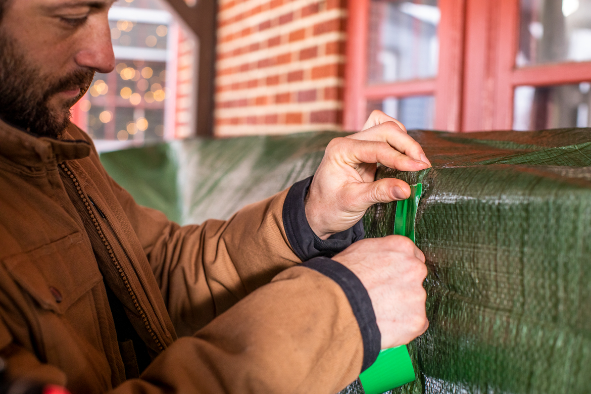 Man repairing green outdoor tarp with green duct tape
