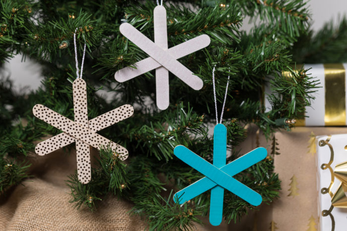 Popsicle snowflake ornaments hanging in a tree.