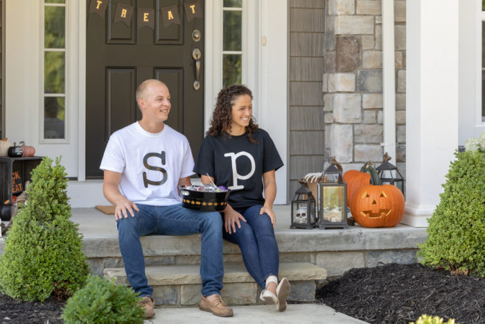 Two people sitting on steps wearing shirts that have S and P on them