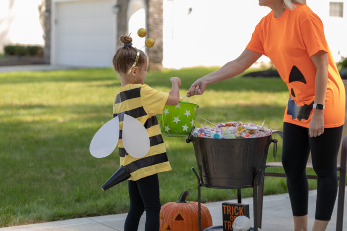 A child in a bumblebee costume getting candy