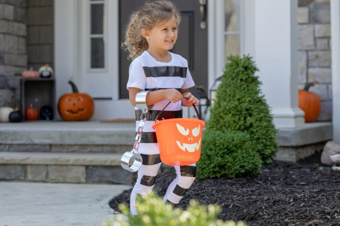 A child dressed a striped Halloween prison's costume.