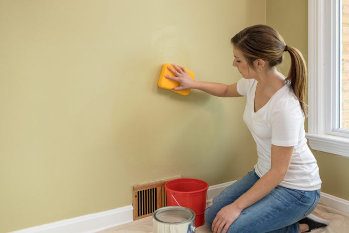 Person washing wall with sponge.