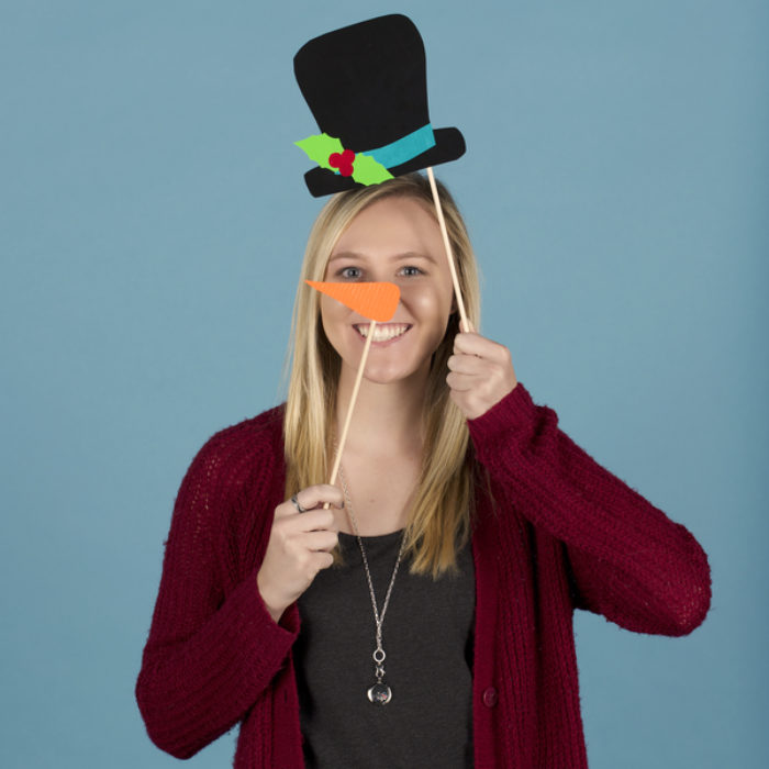 Woman posing with a har and carrot nose  photo booth props made from Duck Tape