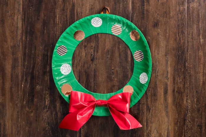 A wreath made out of green Duck Tape with a red Duck tape bow.