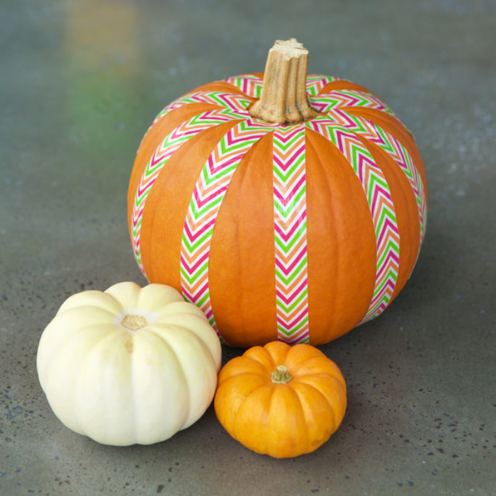A orange pumpkin with colorful Duck Tape on it.