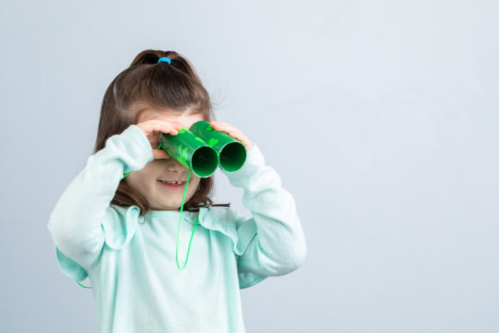 A young girl looking through green duck tape toy binoculars