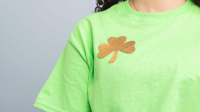 A green t-shirt with a gold shamrock on it.