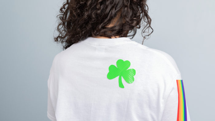 A white shirt with a rainbow sleeve and a green shamrock on it.
