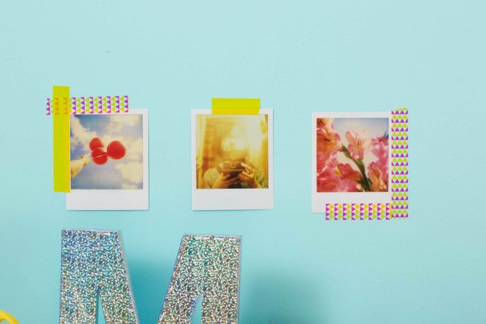 Three pictures on a wall framed with washi tape.