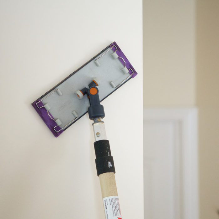 Sanding a wall before painting.