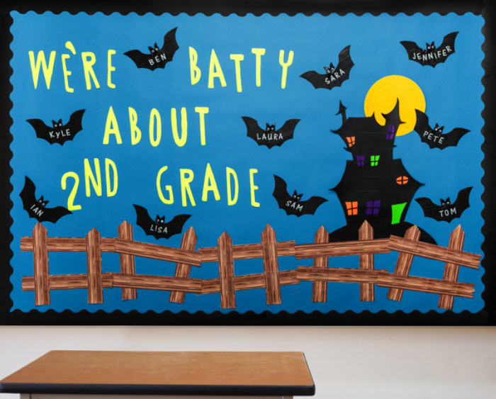 A bulletin board decorated with a spooky castle and bats.