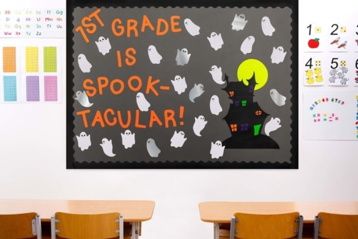 A bulletin board decorated with a spooky castle and ghosts.