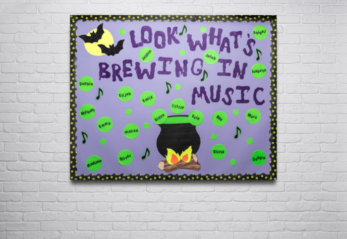 A bulletin board decorated with bats and a spooky cauldron and children's name tags.
