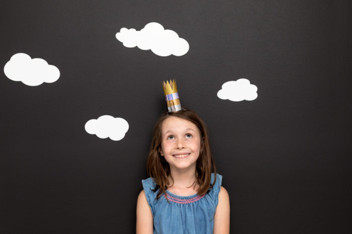 A child wearing a crown made out of a TP roll and colored duck tape.