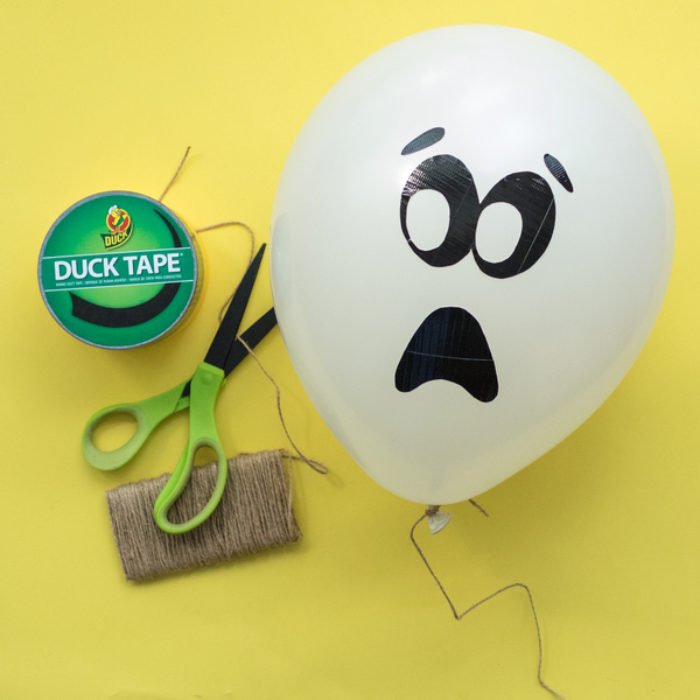 A balloon with a Duck tape ghost face on it, next to a pair of scissors and a roll of Duck Tape.