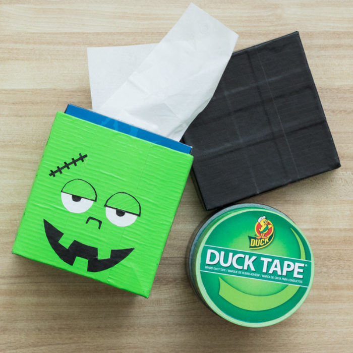 A tissue box covered with green Duck Tape and a monster face.
