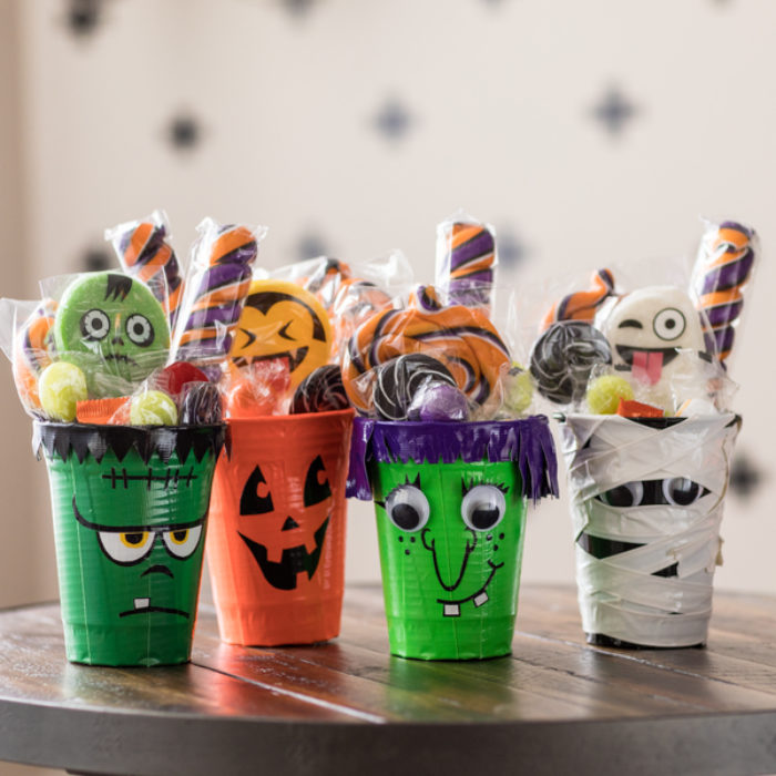 Four cups decorated as monsters with Duck Tape.