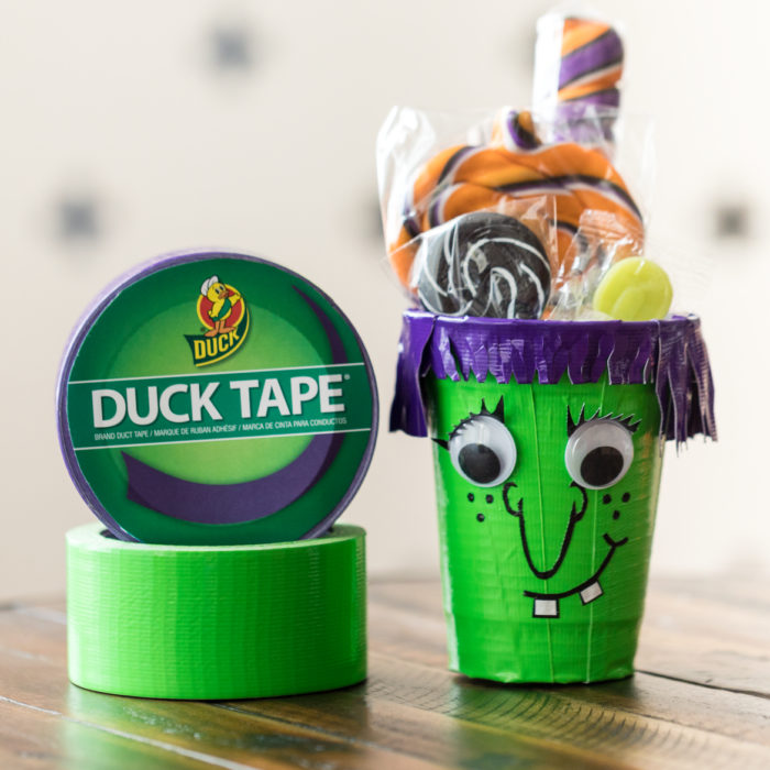 Plastic cup decorated for Halloween with purple and green Duck Tape