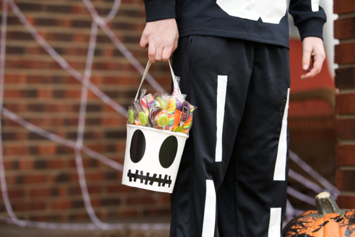 A trick or treat candy bucket decorated as a skeleton skull.