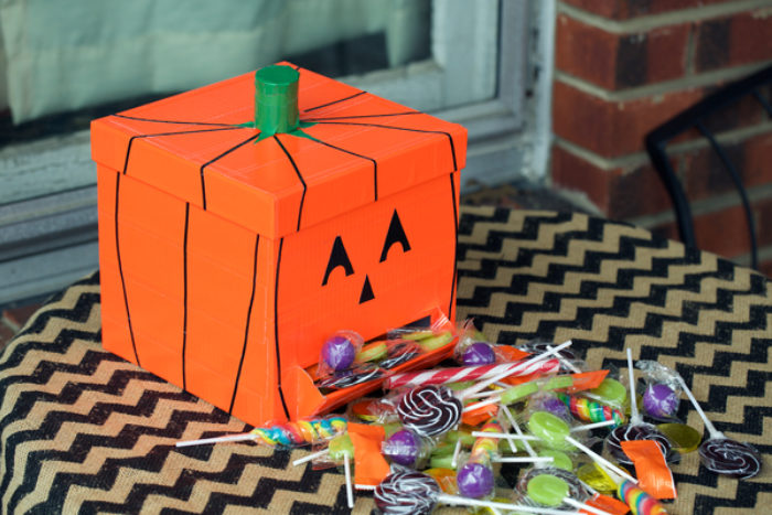 A box decorated as a pumpkin with orange duck tape.
