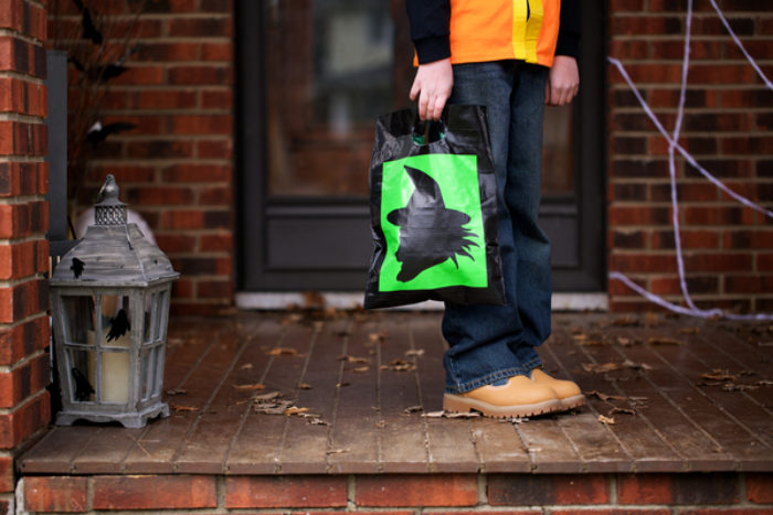 A black and green Trick or Treat bag decorated with colored Duck Tape.