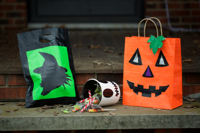 A trick or treat candy bag decorated as a jack-o-lantern.