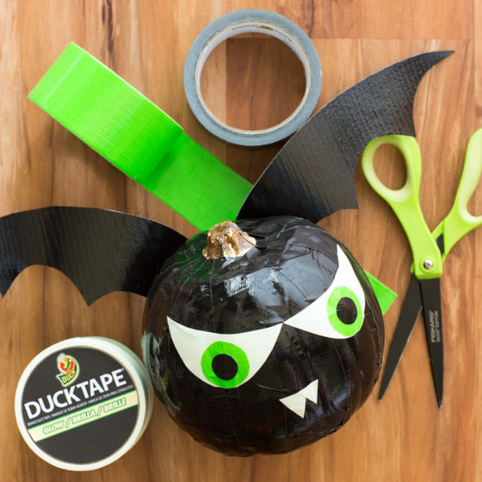 A small black pumpkin decorated as a bat with black and green Duck Tape.