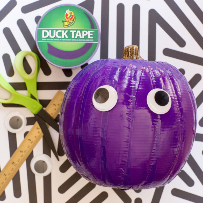 A pumpkin covered with purple Duck Tape with googly eyes on it.