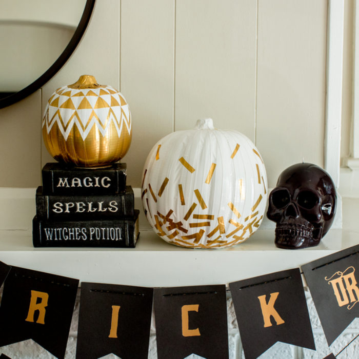 A white pumpkin decorated with gold pieces of Duck Tape in a confetti pattern