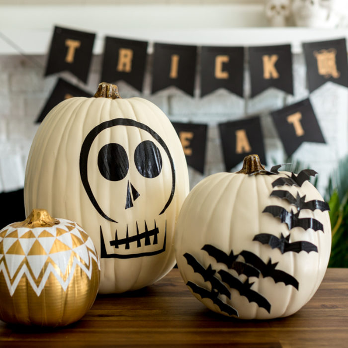 White plastic pumpkins decorated with black Duck Tape.