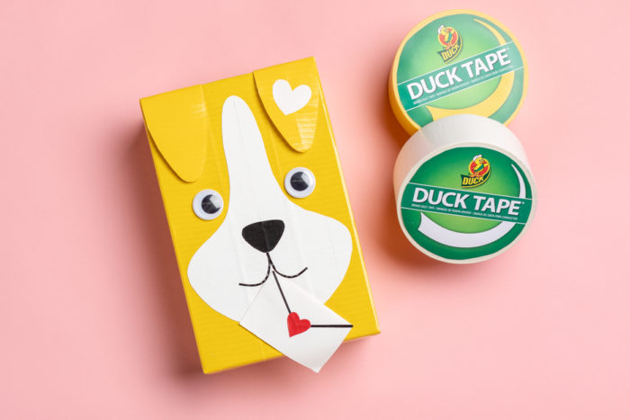 A Valentine's day card box decorated as a dog with yellow Duck Tape.