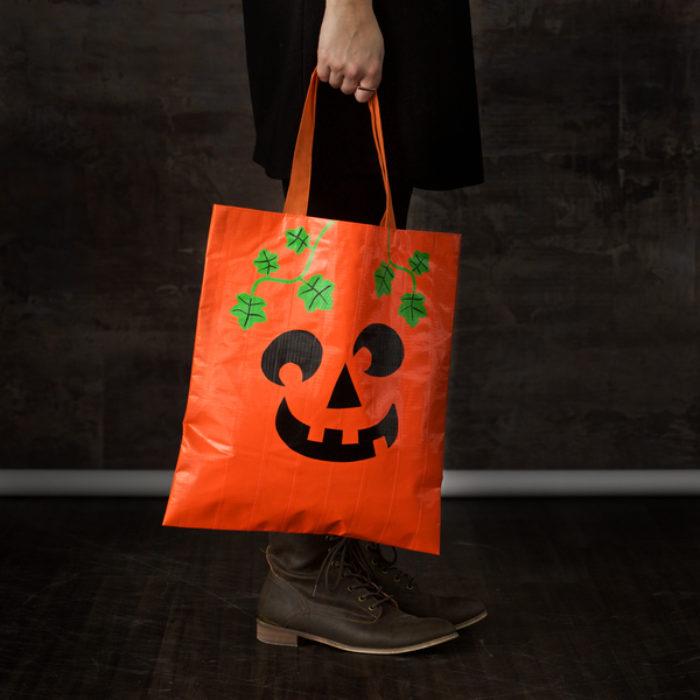 A orange Halloween candy back decorated as a pumpkin.