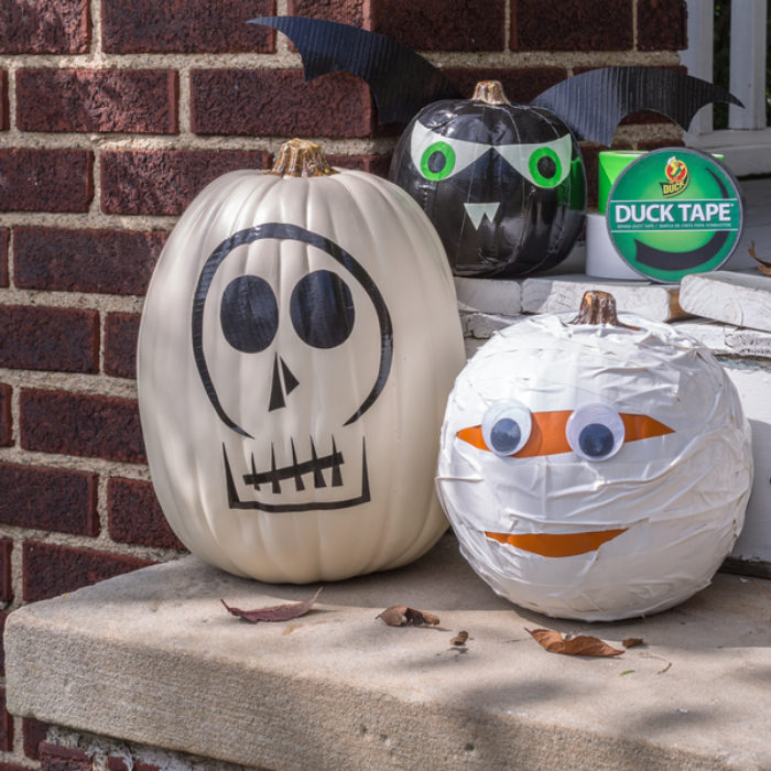 Two plastic pumpkins decorated as a skeleton and a mummy.