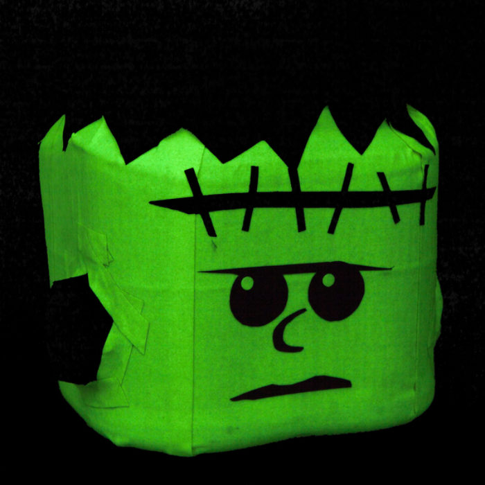 A coffee canister decorated as a monster with green duck tape.