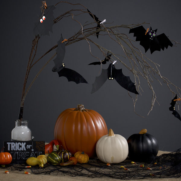 Completed Duck Tape Bat Decorations hanging from a branch, surrounded by Halloween decorations