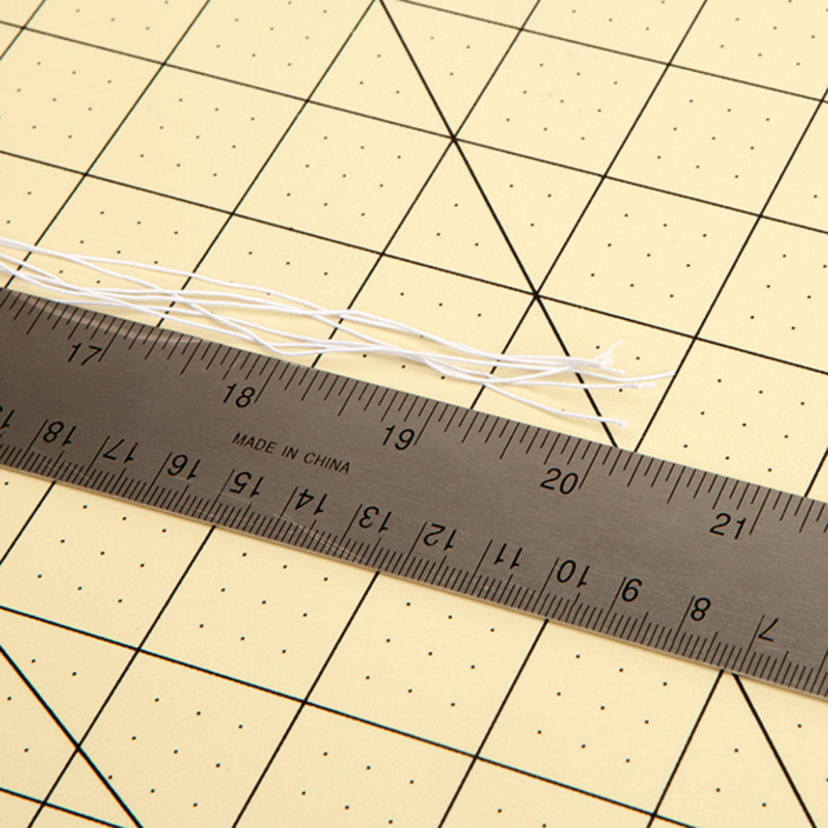7 pieces of elastic cord being measured to ensure that they are 20 inches long