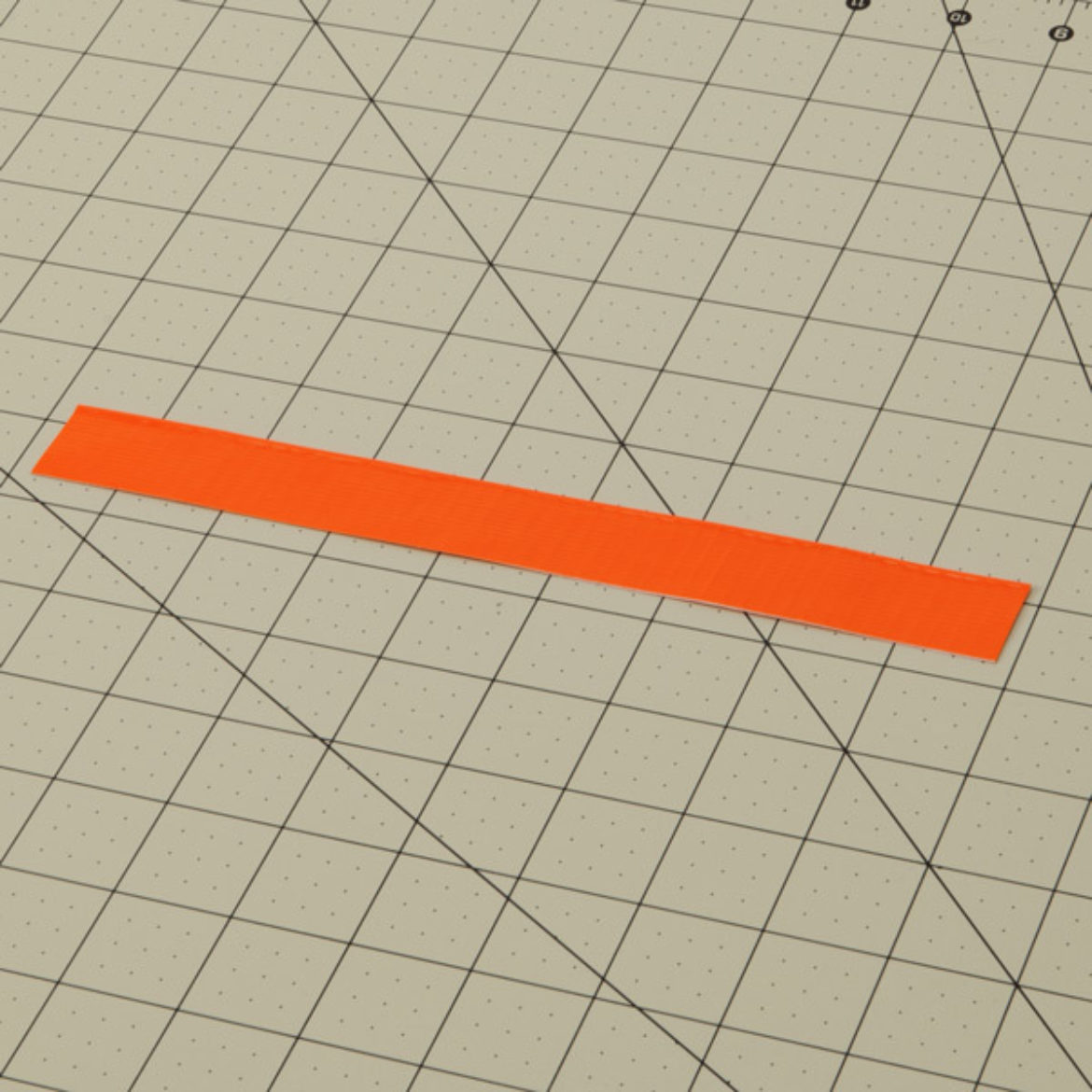 Strip of Orange Duck Tape filded length wise to create a double sided strip of Duck Tape