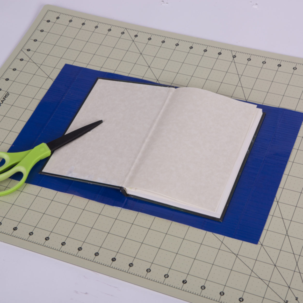 Book of choice placed on the adjoined sheets from the previous step, then cut out the sheet to be the same size as the open book