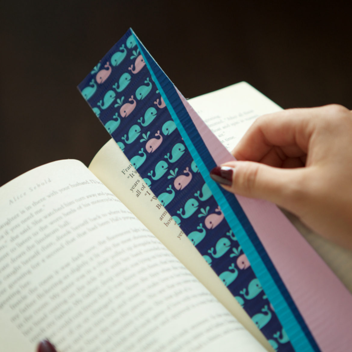 Completed Duck Tape® Bookmark being placed in a book
