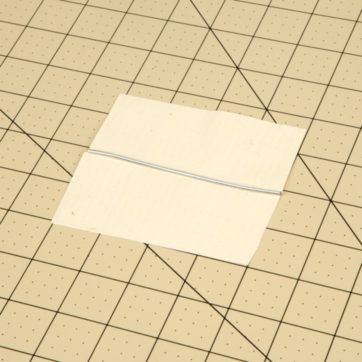 Piece of wire the exact length of the square made in the previous step laid across the center of the square