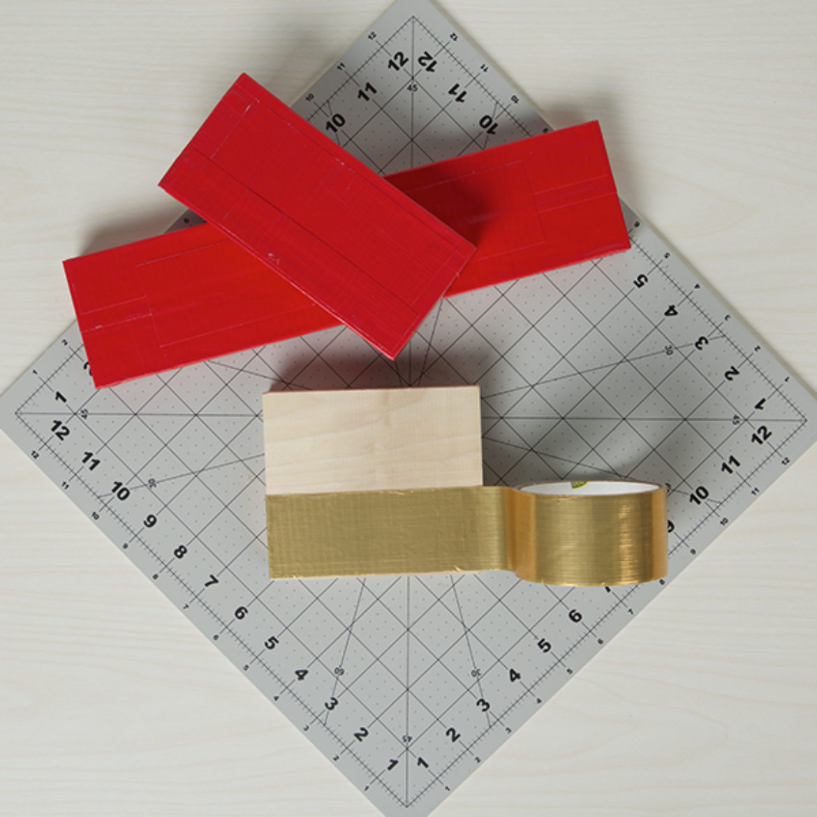 Three blocks covered in red and gold colored Duck Tape