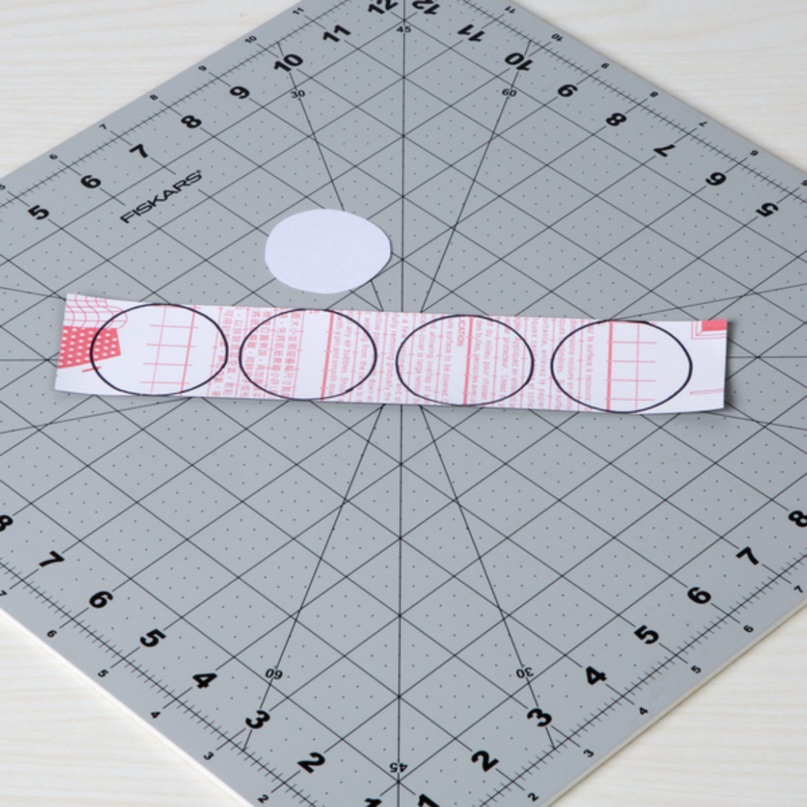 Circles traced on the back of chalkboard tape using the template made in the previous step