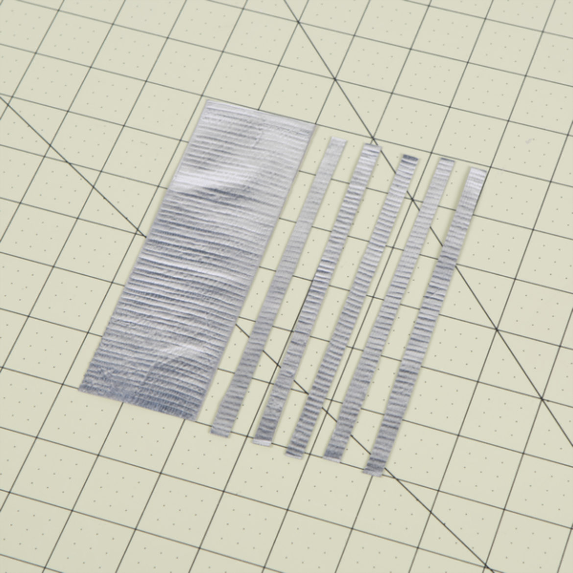 Strip of tape folded over itself length wise and cut into thin strips