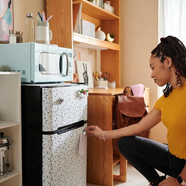 Woman placing EasyLiner shelf liner on dorm mini fridge
