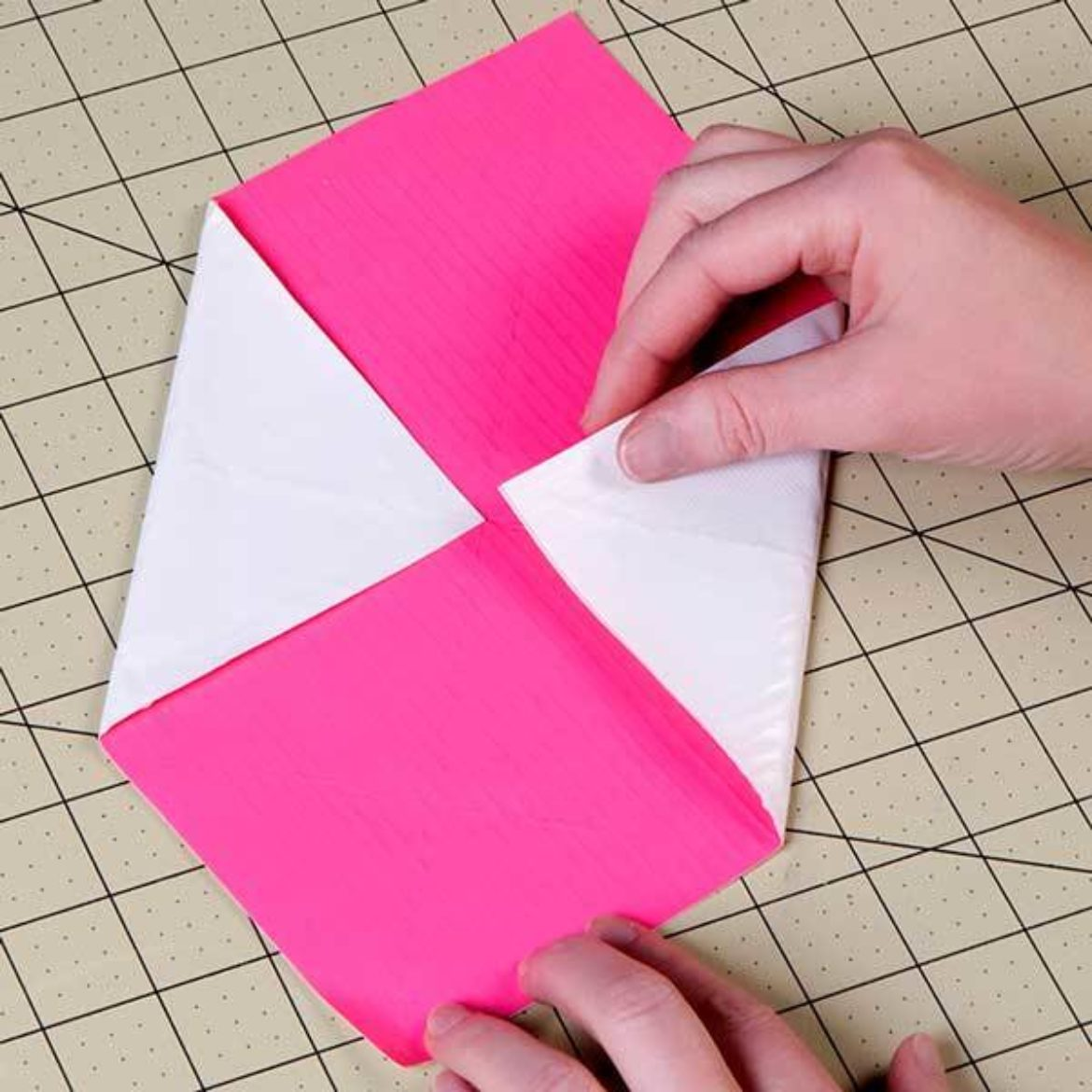 Four corners of the square folded to the center to form a smaller square shape