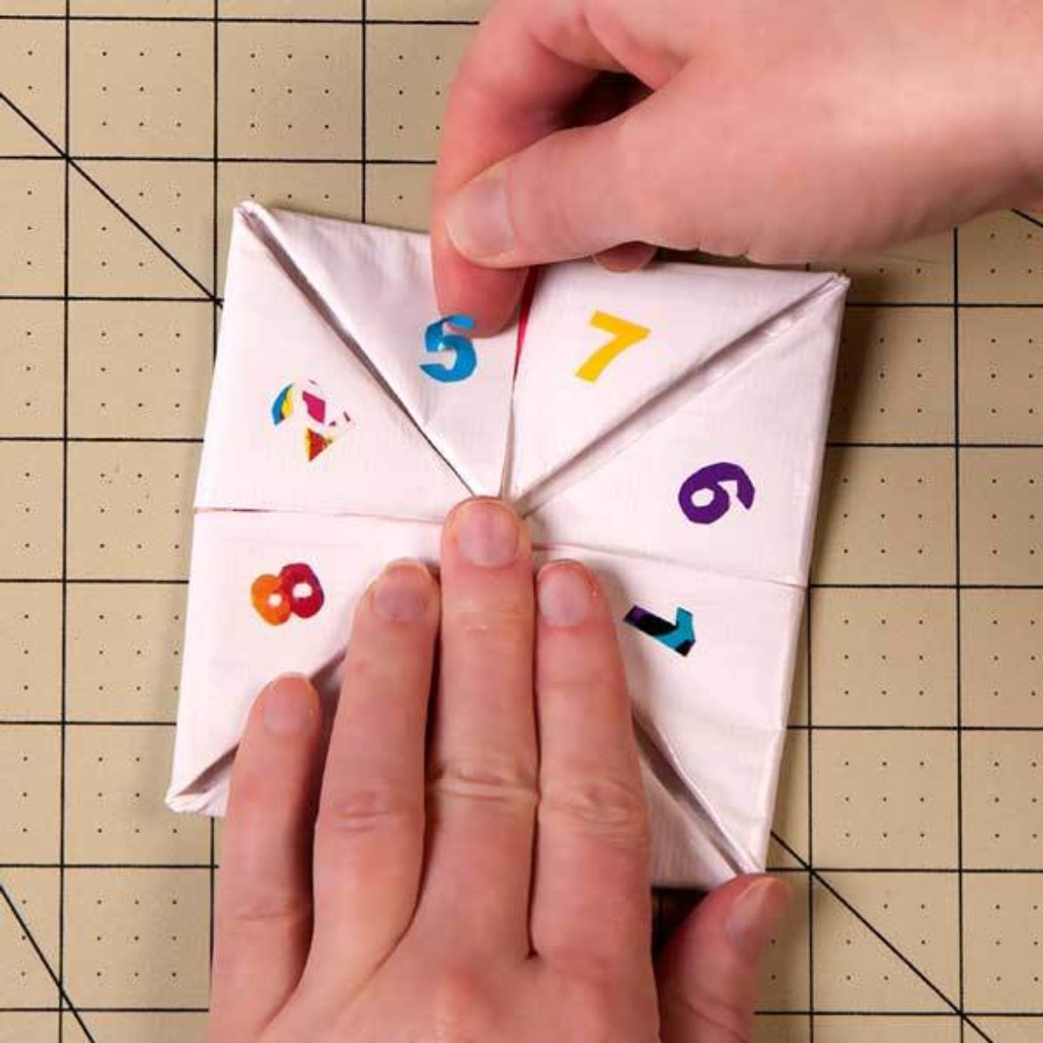 numbers 1-8 cut out of Duck Tape placed on ever triangle shaped fold formed in the square from the previous step